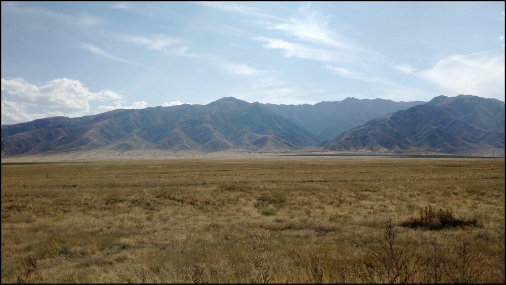 Photo of a large mountain range rising from a flat arid grassy plain