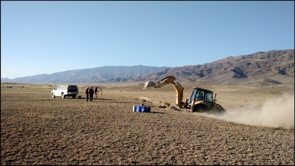 Photo of a vehicle and geologists standing on an arid plain with mountains in the background. In the foreground an excavator digs into a step in the plain, where an active fault has created a scarp